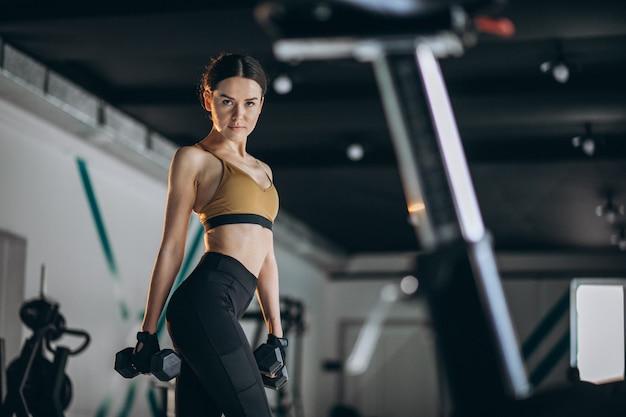 Jonge vrouw fitness trainer in de sportschool
