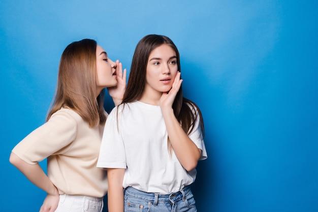 Jonge vrouw fluistert tegen haar partner slecht nieuws geïsoleerd op blauwe muur