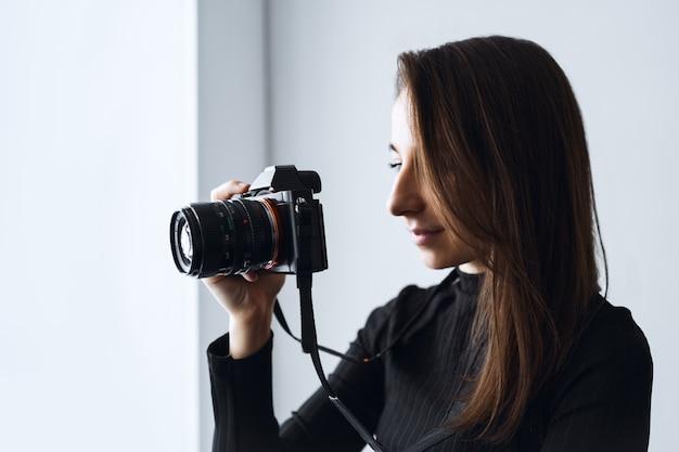 Jonge vrouw fotograaf maakt foto's met moderne digitale camera