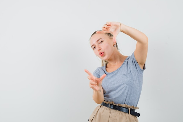 Jonge vrouw frame gebaar maken in t-shirt, broek en op zoek dartel, vooraanzicht.
