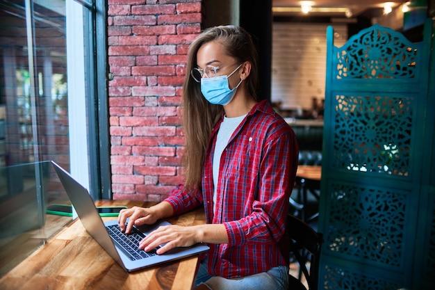Jonge vrouw freelancer die een gezichtsmasker van de geneeskunde draagt dat op afstand werkt op een computer in een café tijdens een pandemie. sociale afstand en bescherming van de gezondheid tegen virussen op openbare plaatsen