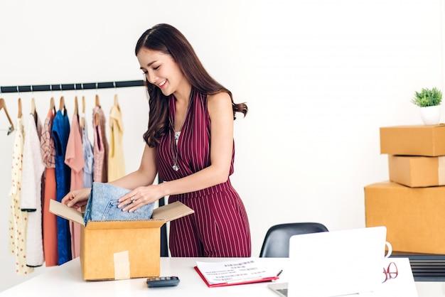 Jonge vrouw freelancer die kleine bedrijfs online winkelen en kleren met kartondoos thuis inpakken - bedrijfs online verschepend en leveringsconcept