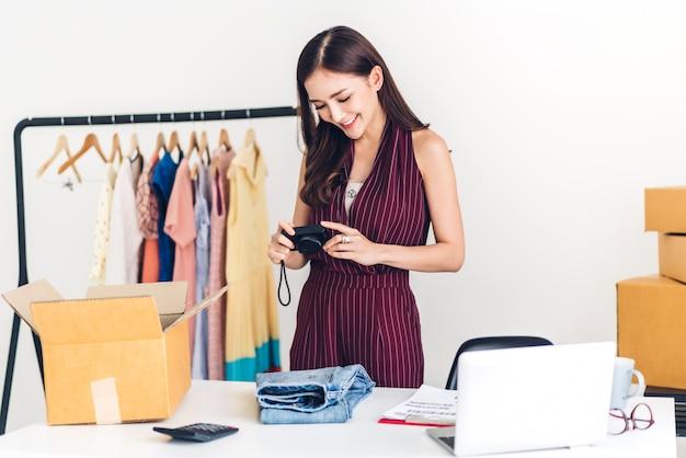Jonge vrouw freelancer die kleine en middelgrote zaken online werken en kleren inpakken