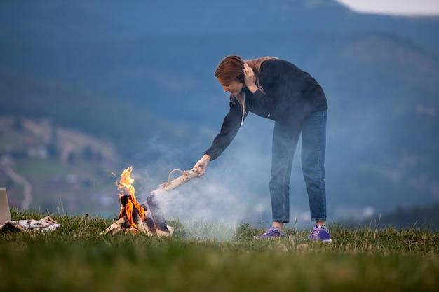 Jonge vrouw freelancer gooit 's avonds brandhout in een brand in de bergen. en toeristenmeisje die openlucht rusten werken