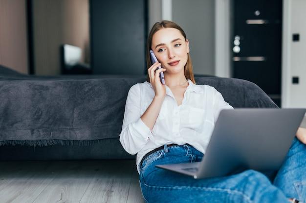 Jonge vrouw freelancer werkt vanuit huis, zittend op de vloer en met behulp van laptop, praten met de klant op de telefoon