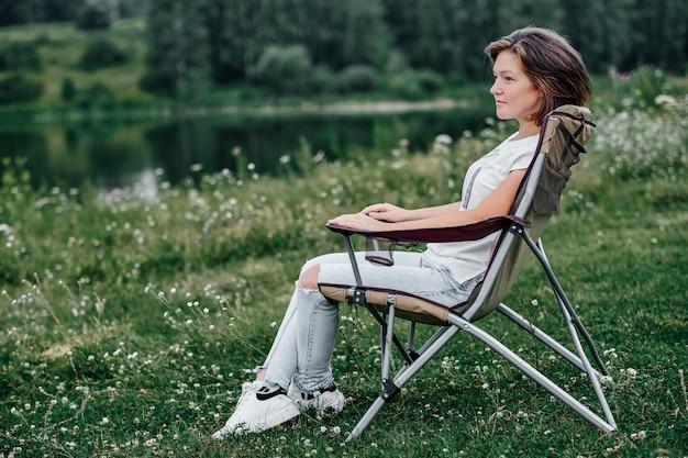Jonge vrouw freelancer zittend op een stoel en ontspannen in de natuur in de buurt van het meer. buitenactiviteiten in de zomer.