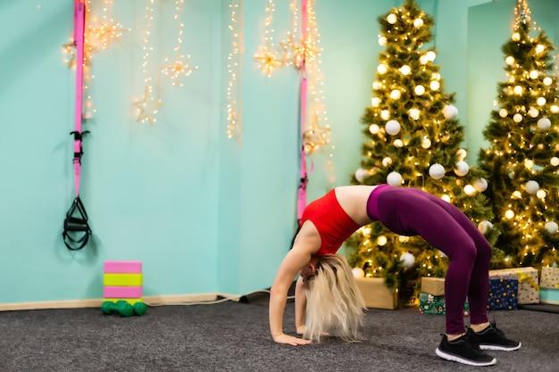 Jonge vrouw gaat sporten bij de kerstboom in de sportschool