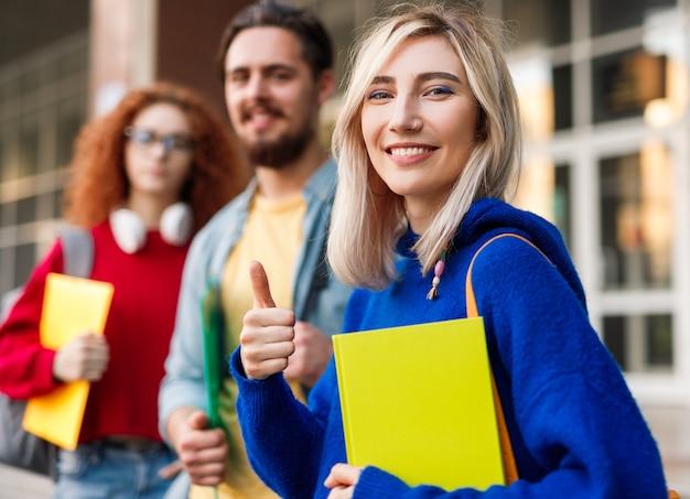 Jonge vrouw gebaren duim omhoog in de buurt van klasgenoten