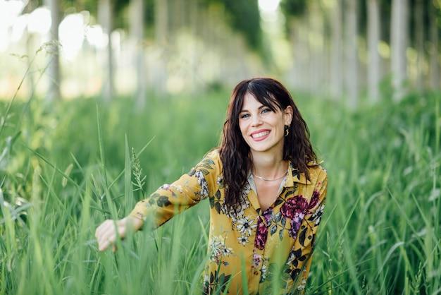 Jonge vrouw, gebloemde jurk dragen, tussen bomen.