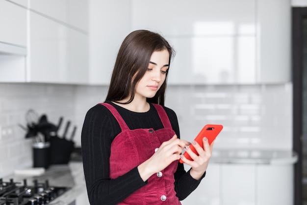 Jonge vrouw gebruikend celtelefoon en hebbend pret in de keuken