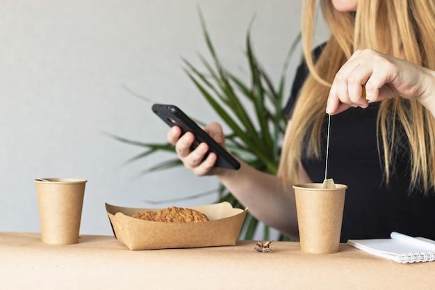 Jonge vrouw gebruikend telefoon en drinkend thee van ecokop
