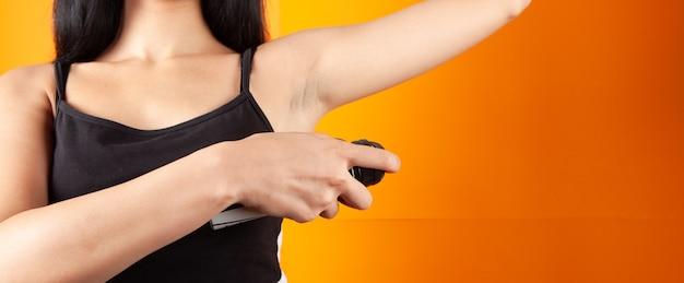 Jonge vrouw gebruikt anti-transpirant oksel