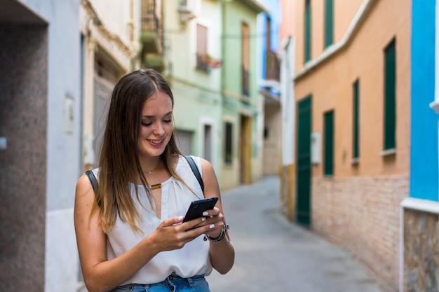 Jonge vrouw gebruikt haar smartphone in de straat