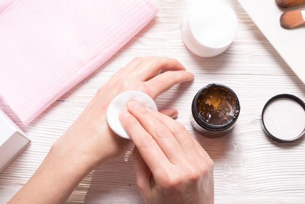 Jonge vrouw gebruikt handcrème, bovenaanzicht