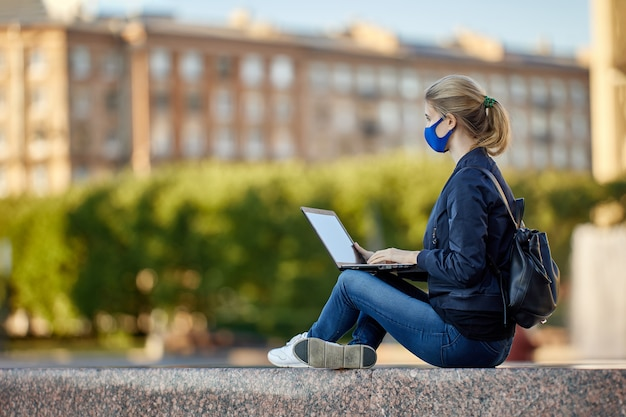 Jonge vrouw gebruikt laptop om buiten op afstand te werken tijdens coronavirusvergrendeling