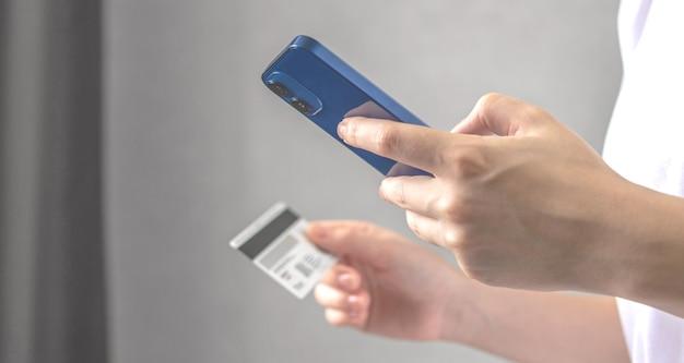 Jonge vrouw gebruikt mobiele telefoon om online te bestellen en rekeningen te betalen met creditcard in het interieur van de woonkamer thuis. smartphone en creditcard ter beschikking close-up, bannerfoto
