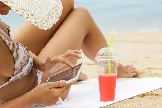 Jonge vrouw gebruikt tablet pc op het strand