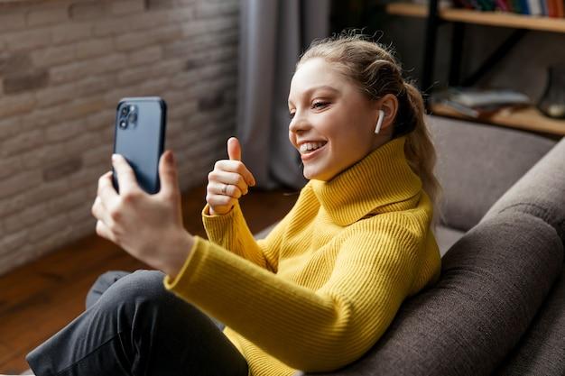 Jonge vrouw gebruikt telefoon voor videogesprek met haar vrienden