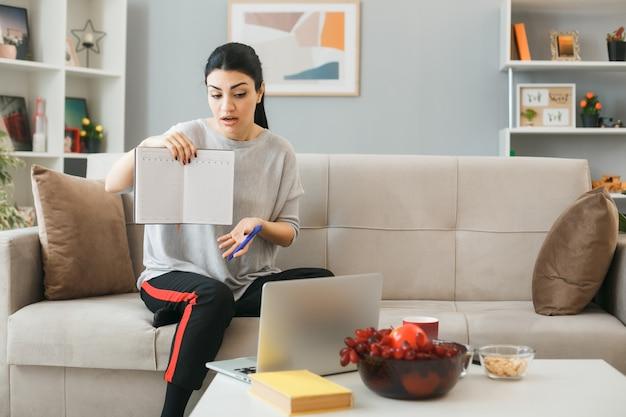 Jonge vrouw gebruikte laptop met notebook zittend op de bank achter de salontafel in de woonkamer