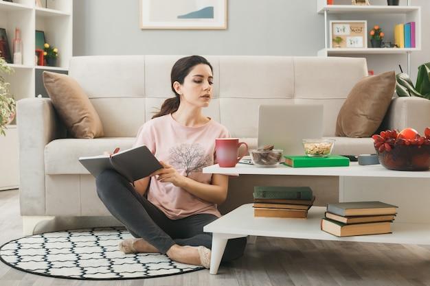 Jonge vrouw gebruikte laptop schrijft op notebook zittend op de vloer achter de salontafel in de woonkamer