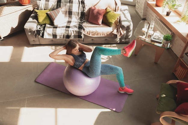 Jonge vrouw geeft thuis online cursussen over fitness, aerobe, sportieve levensstijl tijdens quarantaine. actief worden terwijl je geïsoleerd bent, wellness, bewegingsconcept. oefeningen met fitball voor onderlichaam.