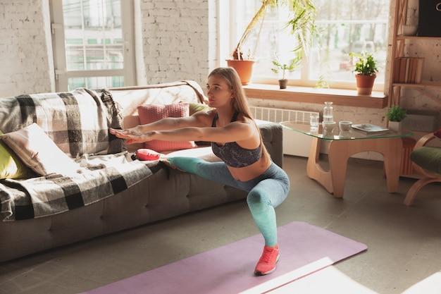 Jonge vrouw geeft thuis online cursussen over fitness, aerobe, sportieve levensstijl tijdens quarantaine.