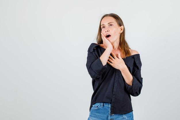 Jonge vrouw geeuwen met handen op de borst en wang in shirt, korte broek vooraanzicht.