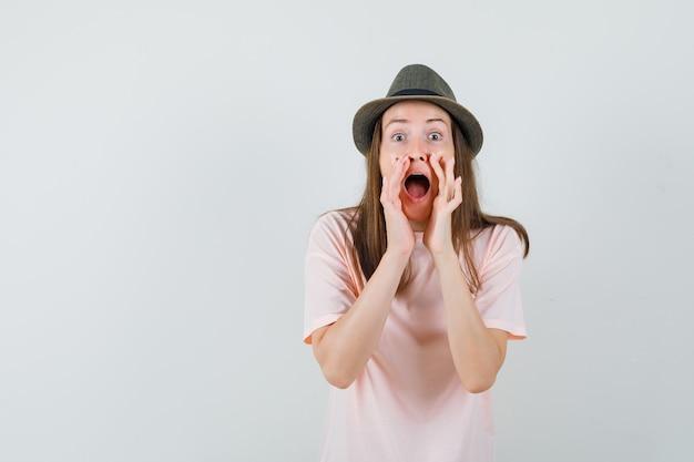 Jonge vrouw geheim vertellen met handen in de buurt van mond in roze t-shirt, hoed vooraanzicht.