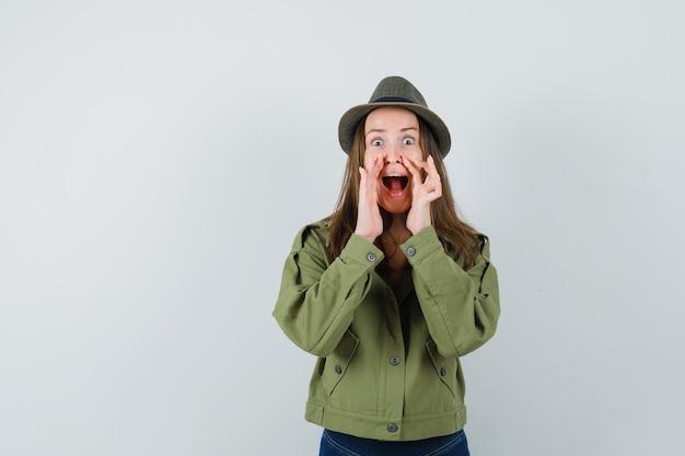 Jonge vrouw geheim vertellen met handen in de buurt van open mond in jas, broek, hoed vooraanzicht.