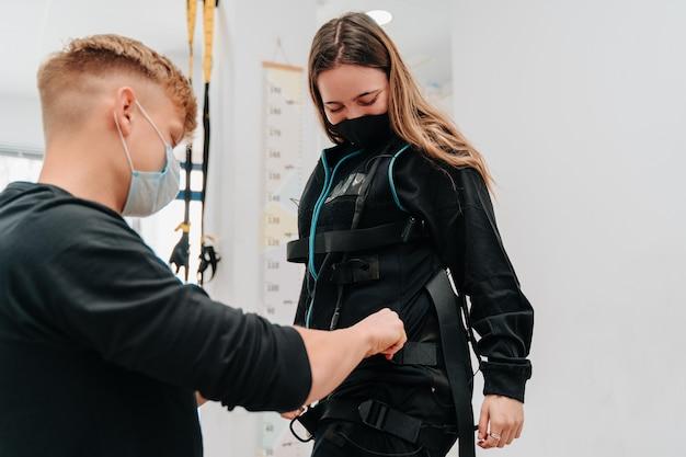 Jonge vrouw geholpen door haar jonge coach terwijl ze haar in het elektrostimulatiepak stopte