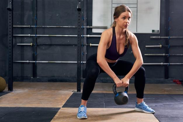 Jonge vrouw gehurkt met gewichten in crossfit gym