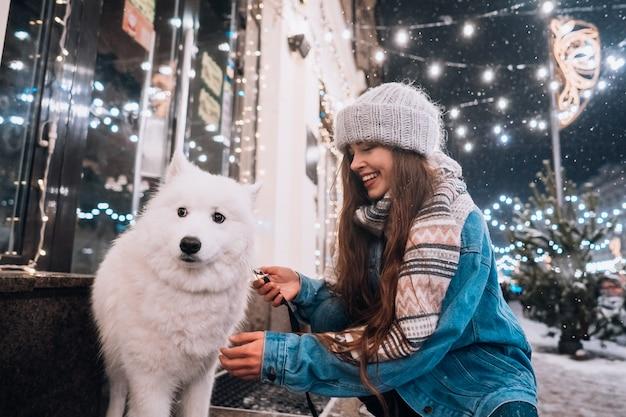 Jonge vrouw gehurkt naast een hond op een winterstraat