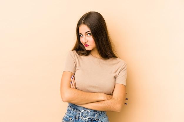 Jonge vrouw geïsoleerd en beige muur verdacht, onzeker, je onderzoekend