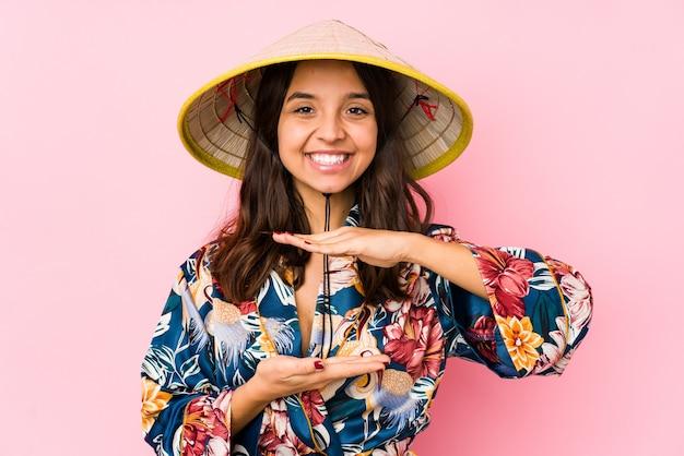 Jonge vrouw geïsoleerd iets met beide handen, productpresentatie te houden