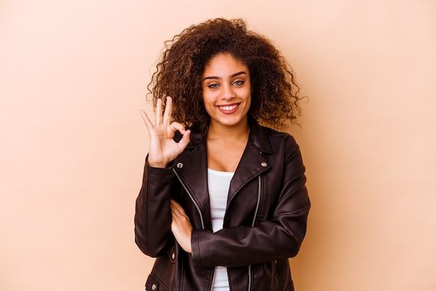Jonge vrouw geïsoleerd op beige muur knipoogt en houdt een goed gebaar met de hand