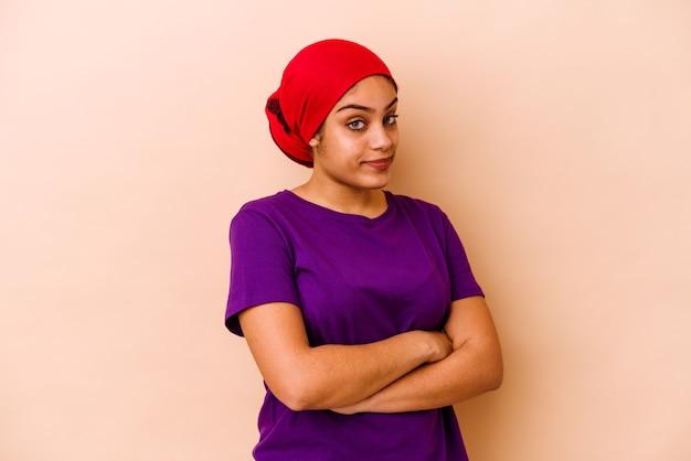 Jonge vrouw geïsoleerd op beige muur ongelukkig in de camera kijken met sarcastische uitdrukking