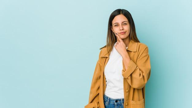 Jonge vrouw geïsoleerd op blauwe achtergrond overweegt, een strategie plannen, na te denken over de manier van een bedrijf.