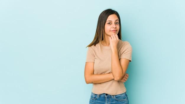 Jonge vrouw geïsoleerd op blauwe achtergrond verdacht, onzeker, u onderzoekt.