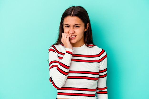 Jonge vrouw geïsoleerd op blauwe muur vingernagels bijten, nerveus en erg angstig