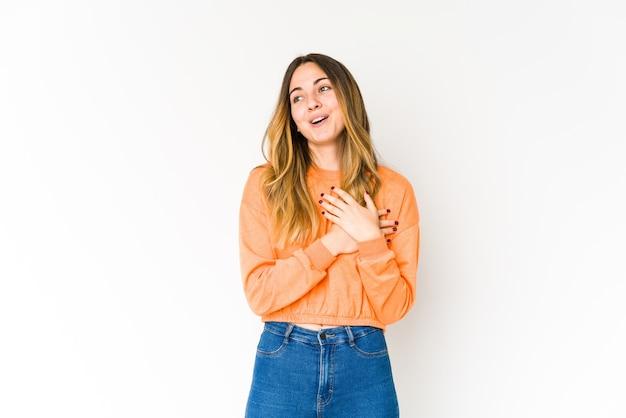 Jonge vrouw geïsoleerd op een witte muur heeft vriendelijke uitdrukking, handpalm tegen borst te drukken