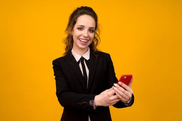 Jonge vrouw geïsoleerd op gele muur achtergrond met behulp van mobiele telefoon