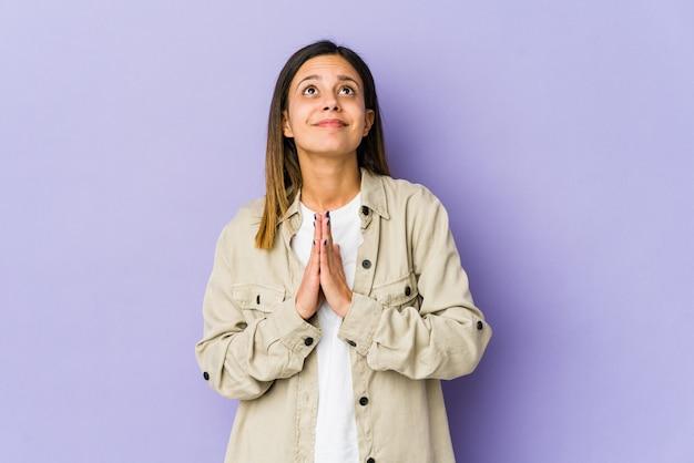 Jonge vrouw geïsoleerd op paarse achtergrond hand in hand bidden in de buurt van de mond, voelt zich zelfverzekerd.