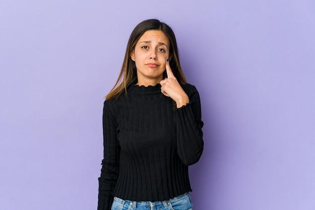 Jonge vrouw geïsoleerd op paarse achtergrond huilen, ongelukkig met iets, pijn en verwarring concept.