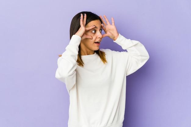 Jonge vrouw geïsoleerd op paarse achtergrond ogen geopend houden om een succeskans te vinden.