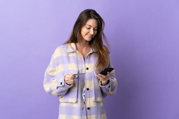 Jonge vrouw geïsoleerd op paarse muur kopen met de mobiel met een creditcard