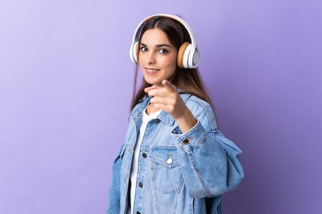 Jonge vrouw geïsoleerd op paarse muur muziek luisteren en naar voren wijzen
