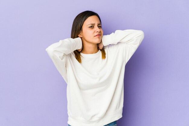 Jonge vrouw geïsoleerd op paarse muur nekpijn lijden als gevolg van een zittende levensstijl.