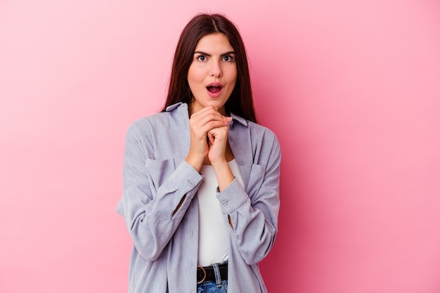 Jonge vrouw geïsoleerd op roze muur bidden voor geluk, verbaasd en mond openen op zoek naar voren