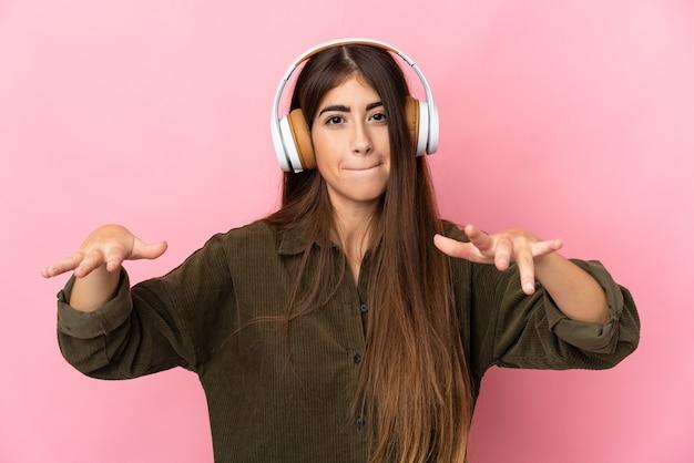 Jonge vrouw geïsoleerd op roze muur luisteren naar muziek en dansen