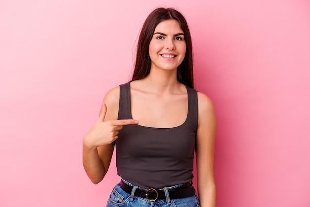 Jonge vrouw geïsoleerd op roze muur persoon met de hand wijzend naar een shirt kopie ruimte, trots en zelfverzekerd